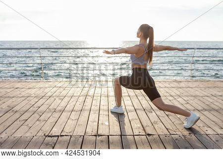 Attractive Young Fitness Woman Practicing Hatha Yoga Exercise At Sunrise On The Beach