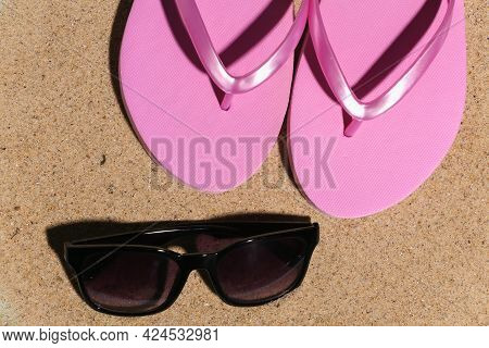 Summer Beach Travel Vacation Concept. Flip Flops With Sunglasses On Sand At Bright Sunny Day. Top Vi