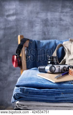 Denim jeans and vintage camera at chair.  Stack of jeans at abstract background texture surface