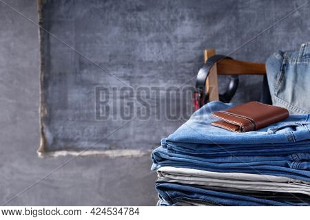 Denim jeans and leather wallet or bag at chair.  Stack of jeans near abstract background texture surface
