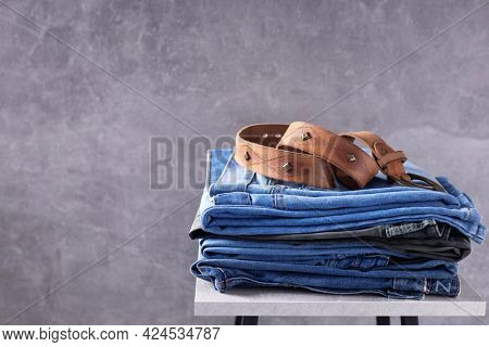Denim jeans and leather belt at chair. Stack of jeans near abstract background texture surface