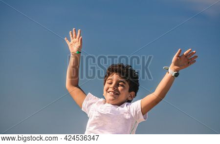 Happy Little Boy With Raised up Hands Having Fun Outdoors. Nice Child with Joy Spending Holidays in Summer Camp. Happiness and Freedom Concept.