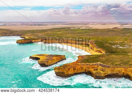 Helicopter flight over the scenic Pacific coastline. The fabulous journey to Australia. Cloudy cool summer day. Legendary cliffs