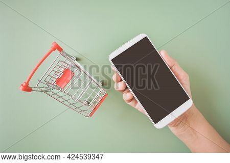 Human's Hand Holding Smart Phone With Clipping Path On Touchscreen And Blurred  Empty  Shopping Cart