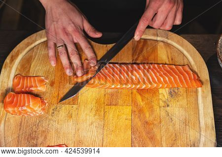 Closeup Chef Hands Slicing Fresh Fish Slice On The Wooden Cutting Board
