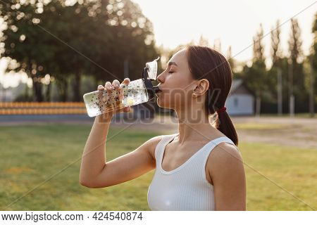Profile Portrait Of Fe Male With Dark Hair And Ponytail Wearing White Top Posing Outdoors And Drinki
