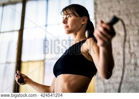 Sporty woman jumping skipping rope at gym