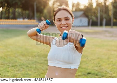 Portrait Of Happy Satisfied Smiling Female Wearing White Top Holding Out Dumbbell To Camera, Trainin