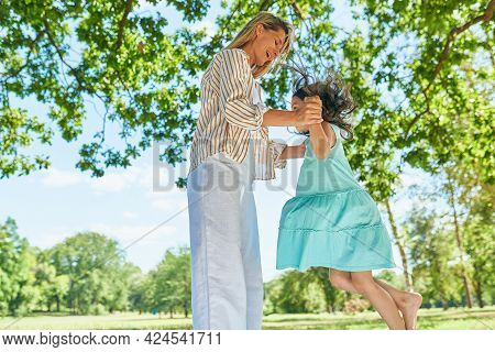 Little Girl Playing And Jumping With Her Mother In The Park On The Grass During The Picnic. Loving W