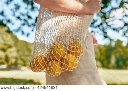 A Young Woman Dresssed In Lineen Dress With The Eco Friendly Bag With Lemons Walking Outdoor On Natu