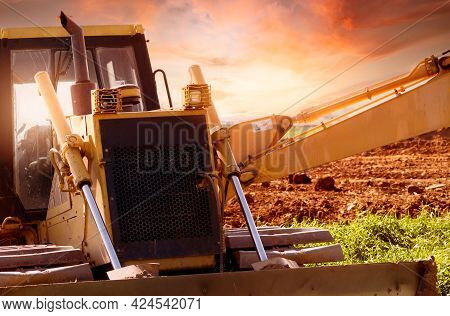 Selective Focus On Bulldozer On Blur Background Of A Backhoe At Construction Site. Excavation Vehicl