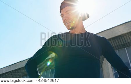 An Athlete In Sportswear With Hands On The Waist Posing On A Sunlight. Portrait Of An Athletic Man T