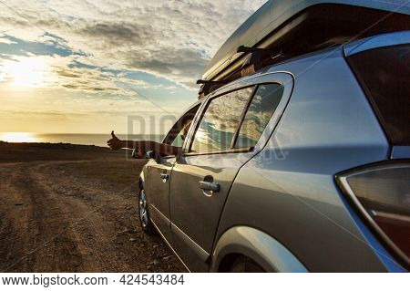 Travel To The Sea By Car. The Girl Stuck Out Her Hand. Thumb As A Sign Of Pleasure