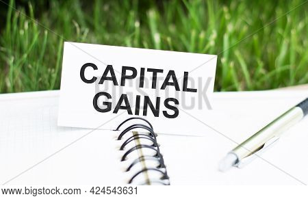 Text Capital Gains On White Card, Which Lies On An Open Notebook. Business And Financial Concept