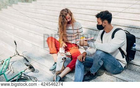 Two Young Students In Protective Face Masks Sitting On The Stairs Of The College Campus Outside And