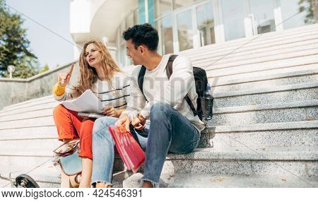 Horizontal Image Of A Young Woman And A Man Sitting On The Stairs Of The University For Team Work. T