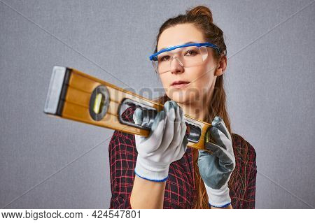 Sexy Longhaired Woman In Casual Clothes Protective Gloves Hold Spirit Level In Hand. Studio Portrait
