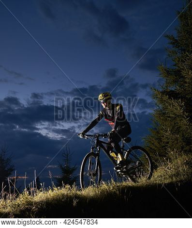 Smiling Young Man Riding Bicycle Downhill With Beautiful Blue Evening Sky On Background. Bicyclist I