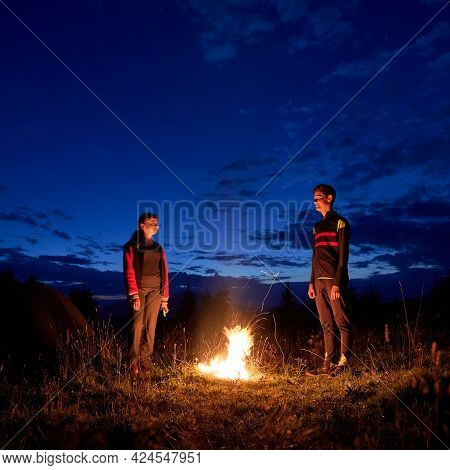 Young Couple Of Tourists Spending Time Together In Camping. Young Man And Woman Having A Rest Near C