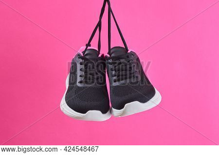 Pair Female Sports Sneakers For Run And Fitness Hanging By Shoelaces On Pink Background. Fashion Sty