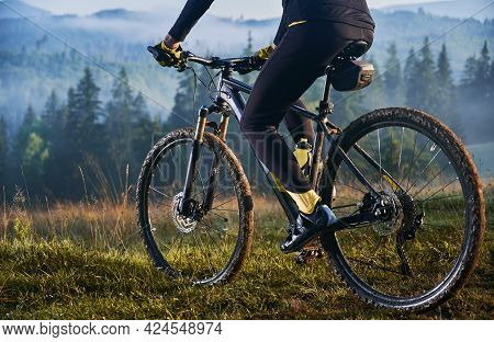 Cropped View Of Man In Cycling Suit Riding Bicycle On Grassy Hill. View Of Majestic Mountains On The