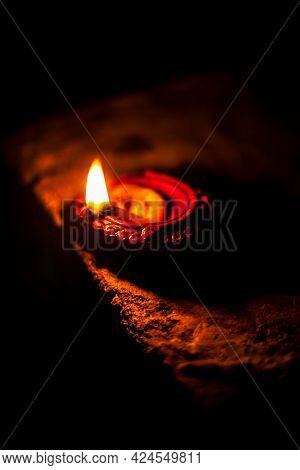 Close-up Shot Of Burning Diva Or Divida Or Diya Or Oil Lamp Isolated In Dark.