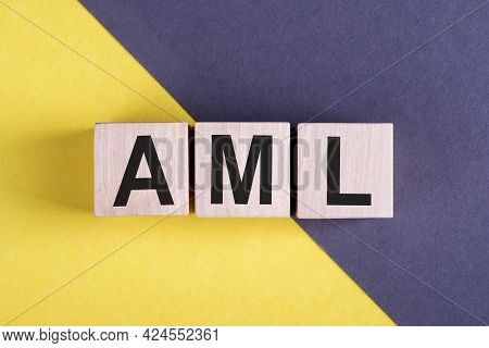 Word Aml - Anti-money Laundering, Wooden Cubes, Over Yellow And Blue Background.