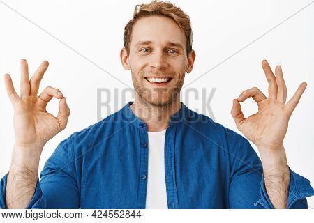 Close Up Portrait Of Satisfied Redhead Man, Smiling And Looking Happy, Showing Ok Okay Gesture To Pr