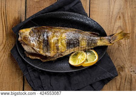 Baked Sea Bass Or Lingcod Fish On A Black Plate And Old Wooden Background Top View