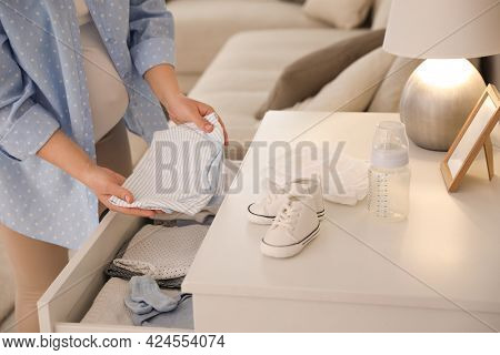 Pregnant Woman Taking Bodysuit From Commode At Home, Closeup