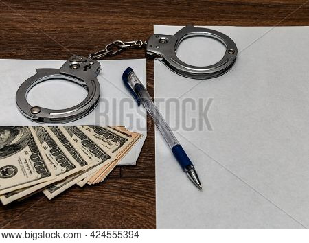 Handcuffs, An Envelope With Dollars, A Pen And A Blank Sheet Of Paper On A Wooden Table. Frank Confe