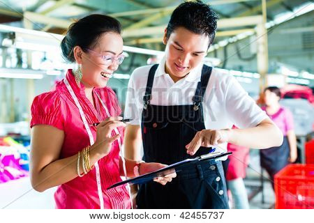 Worker or foreman and dressmaker or designer look on a Clipboard in a factory