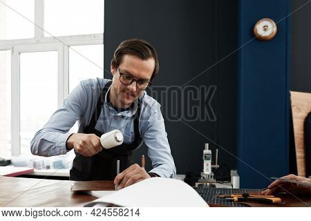 A Tailor With Glasses In A Shirt And An Apron In A Workshop, A Man Tailor Is Engaged In Leather Dres