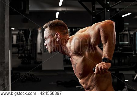 A Man With Sports Aggression Doing Press On The Uneven Bars In A Gym, Training Pectoral Muscles And