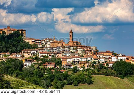 View of small town of Govone on the hill under beautiful cloudy sky in Piedmont, Northern Italy.