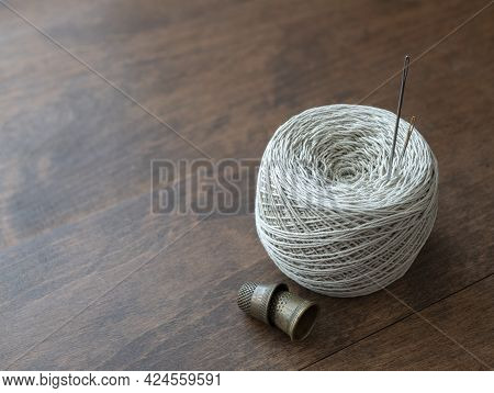 Cotton Thread Reel, Needles And Thimbles On The Wooden Surface. Needlework Supplies