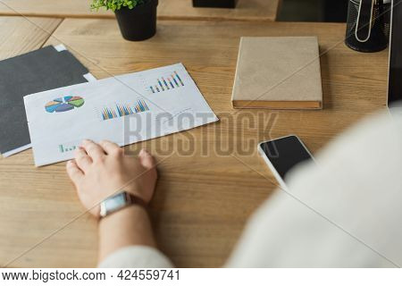 Partial View Of Male Hand In Wristwatch Touching Paper With Graphs And Charts Near Cellphone On Wood