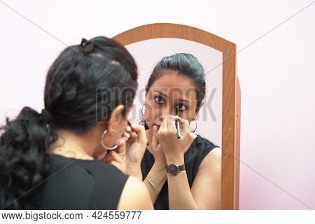 A Lady In 30s Putting Leye Liner Make Up In Front Of A Mirror