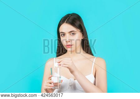 Girl Take Some Pills, Holds Glass Of Water, Isolated On Blue. Young Woman Taking Pill Against Headac