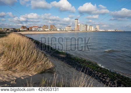 Waterfront, Dunes And View On Vlissingen City With Sandy Beach On Sunset