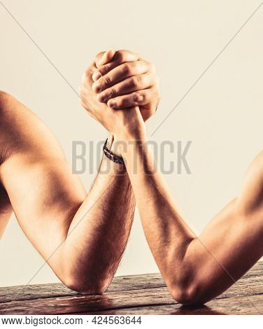 Two Mans Hands Clasped Arm Wrestling, Strong And Weak, Unequal Match. Arm Wrestling. Heavily Muscled
