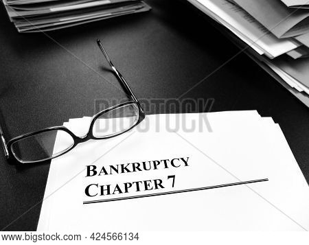Bankrupcty documents for Chapter 7 on Desk with glasses for planning