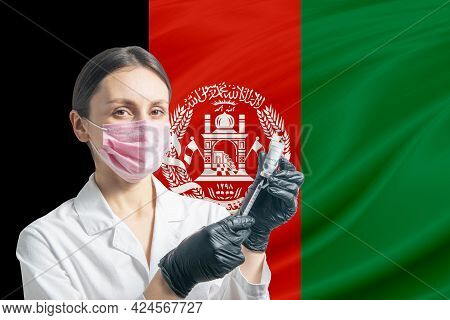 Girl Doctor Prepares Vaccination Against The Background Of The Afghanistan Flag. Vaccination Concept
