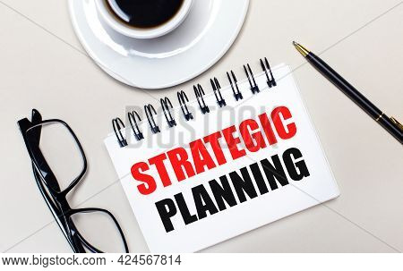 Glasses, A White Cup Of Coffee, A White Notebook With The Words Strategic Planning And A Ballpoint P