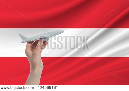 Airplane In Hand With National Flag Of Austria. Travel To Austria.