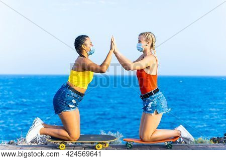 Two Female Friends With Protective Masks Playing With Skateboard. Girlfriends Celebrating Their Succ
