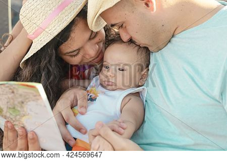 Smiling Mother And Father Holding Their Newborn Baby. Family Concept.