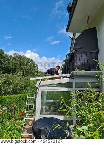 Man Cleaning Conservatory With A Pressure Washer - High Pressure Washer On Patio Glass Surface