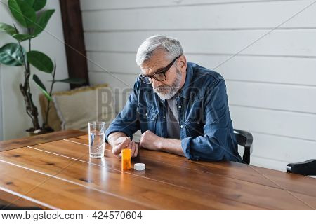Lonely Senior Man Holding Pill Near Water On Table