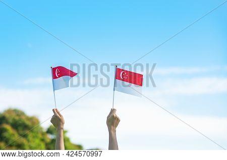 Hand Holding Singapore Flag On Blue Sky Background. Singapore National Day And Happy Celebration Con